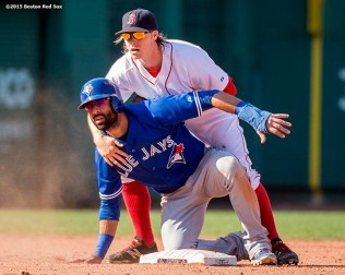 """Boston Red Sox second baseman Brock Holt turns a double play over right fielder Jose Batista during the eighth inning of a game against the Toronto Blue Jays at Fenway Park in Boston, Massachusetts Monday, September 7, 2015."""