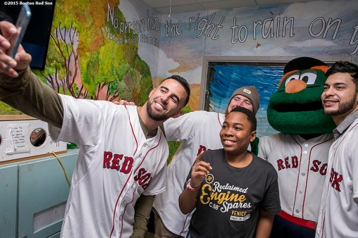 """Boston Red Sox infielder Deven Marrero, pitcher Robbie Ross Jr. and Noe Ramirez, and mascot Wally the Green Monster pose for a selfie photograph with a patient at Boston Medical Center during the Holiday Caravan in Boston, Massachusetts Friday, December 10, 2015."""