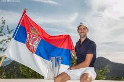 """Novak Djokovic poses for a photograph with the flag of Serbia after defeating Milos Raonic in the men's finals during the 2016 BNP Paribas Open at the Indian Wells Tennis Garden in Indian Wells, California Sunday, March 20, 2016."""
