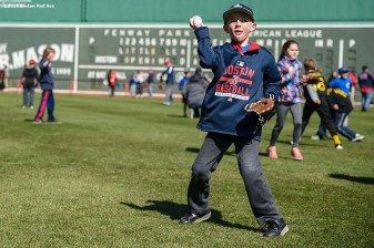 """A fan plays catch in the outfield during Little League Opening Day at Fenway Park in Boston, Massachusetts Saturday, April 9, 2016."""