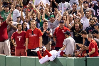 BOSTON, MA - JUNE 13: Mookie Betts #50 of the Boston Red Sox falls over the wall after catching a fly ball during the tenth inning of a game against the Philadelphia Phillies on June 13, 2017 at Fenway Park in Boston, Massachusetts. (Photo by Billie Weiss/Boston Red Sox/Getty Images) *** Local Caption *** Mookie Betts