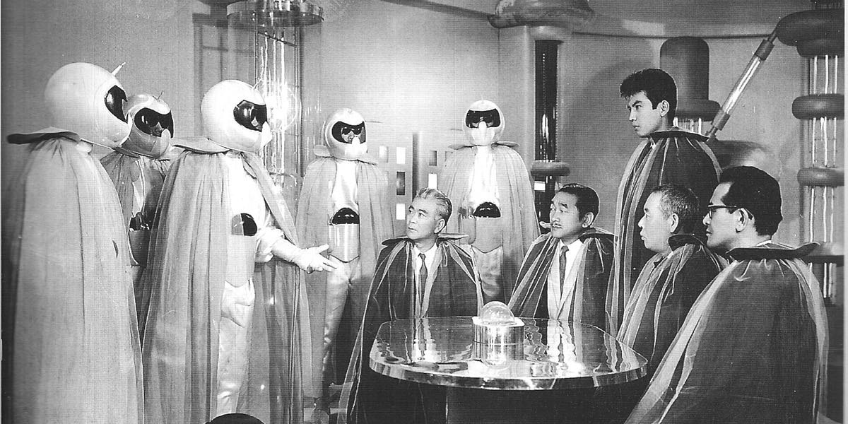 A shot of The Mysterians and human scientists sitting around a table wearing wonderful capes