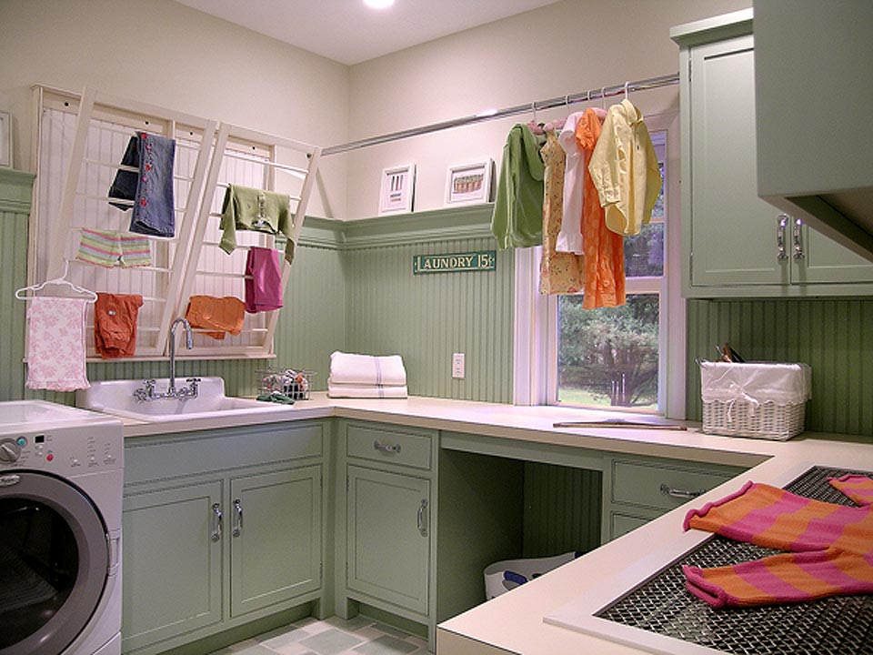 Cheerful laundry room features frameless, shaker style, custom pale green painted cabinets by Bilotta, matching pale green wainscoting and molding and ivory quartz countertops. Ivory wall-mounted dryer racks above the sink and a silver clothing rod add to the functionality of the space. Design by Randy O'Kane, CKD, of Bilotta Kitchens.