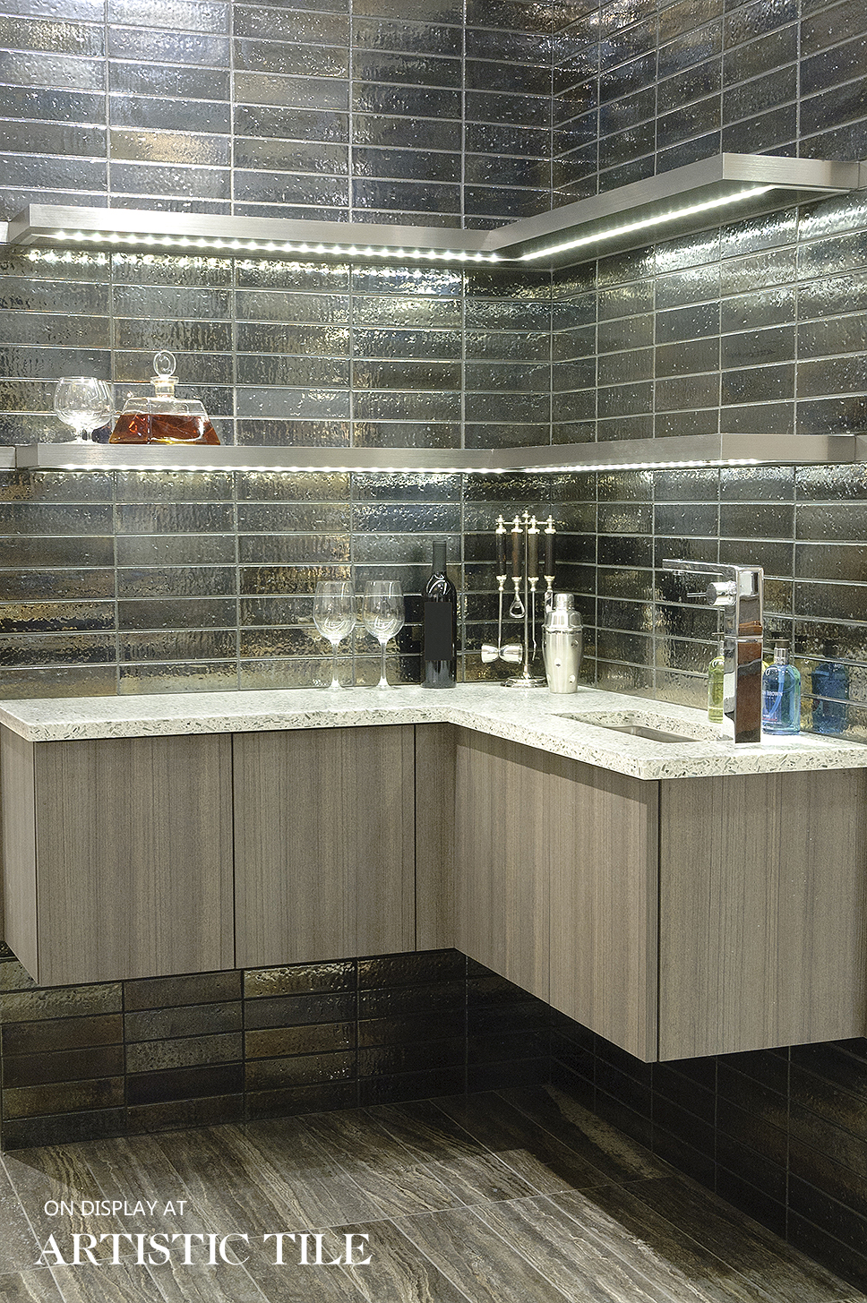 Modern wet bar features silver iridescent tile by Artistic Tile, vertical grained laminate bar with quartz countertop and underlit floating shelves. design by RitaLuisa Garces of Bilotta Kitchens.