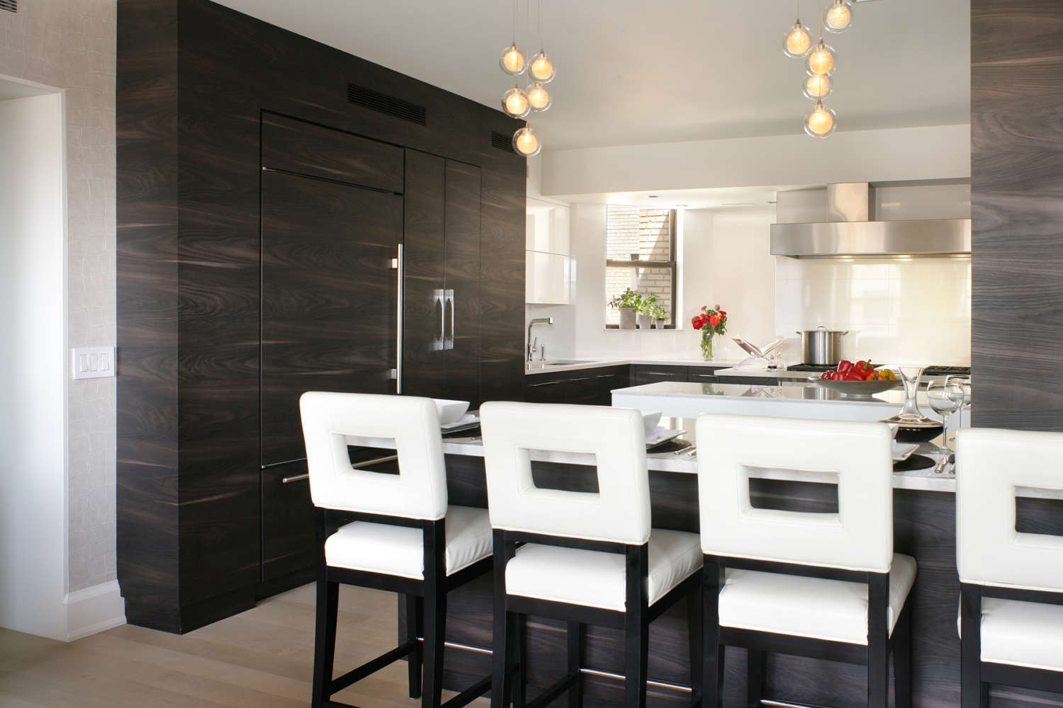 Contemporary kitchen features fully custom flat panel, frameless Artcraft Cabinetry in mix of pure white gloss and Yosemite Scuro laminate, and island and a large peninsula with seating. Design by RitaLuisa Garces of Bilotta Kitchens.