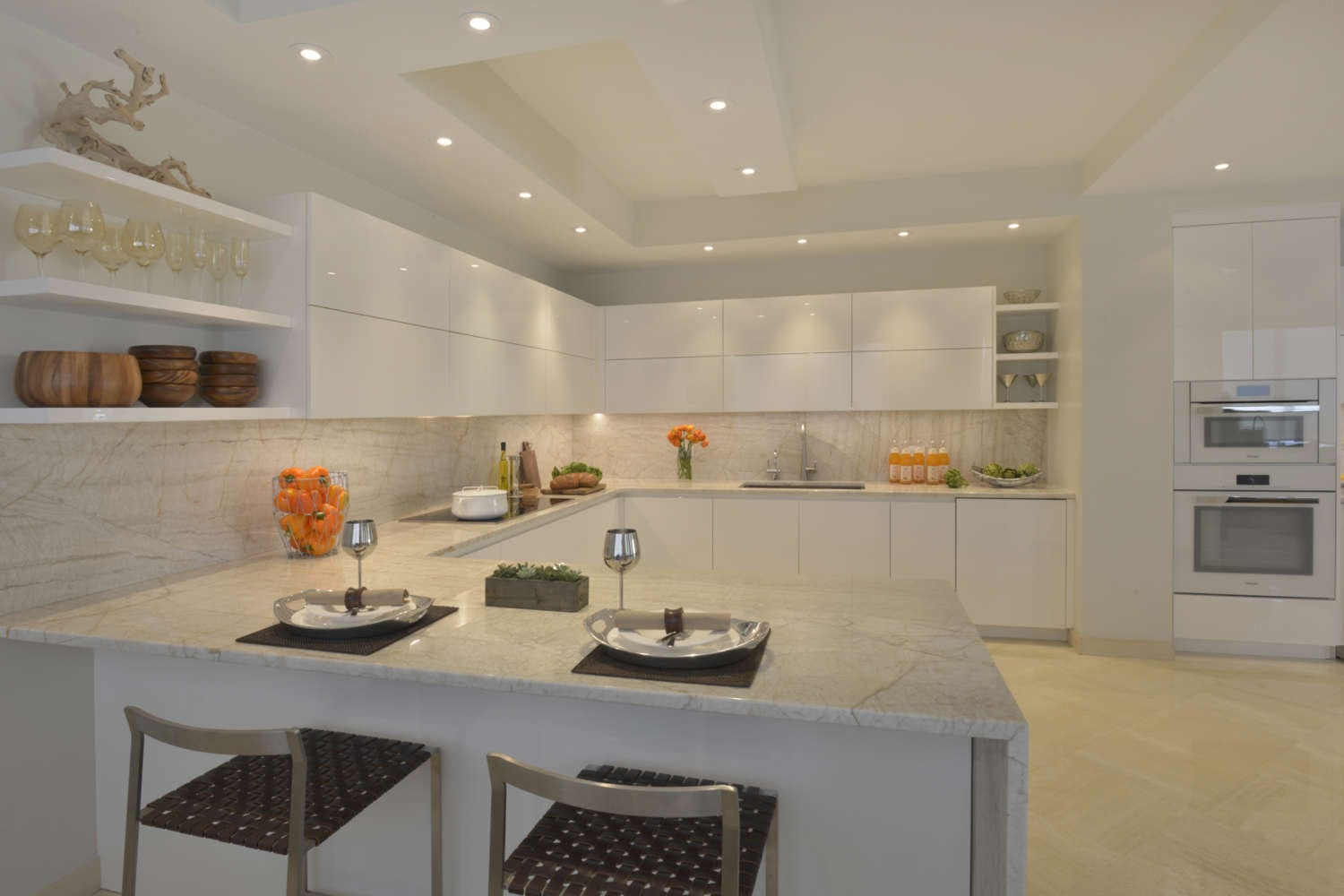 U-shaped kitchen incorporates seating, open shelving and clean lines. The room features fully custom cabinets are high gloss white, flat panel, frameless design by Artcraft, light marble countertop and backsplash with veining and light porcelain tile flooring. Design by Tabitha Tepe of Bilotta Kitchens.