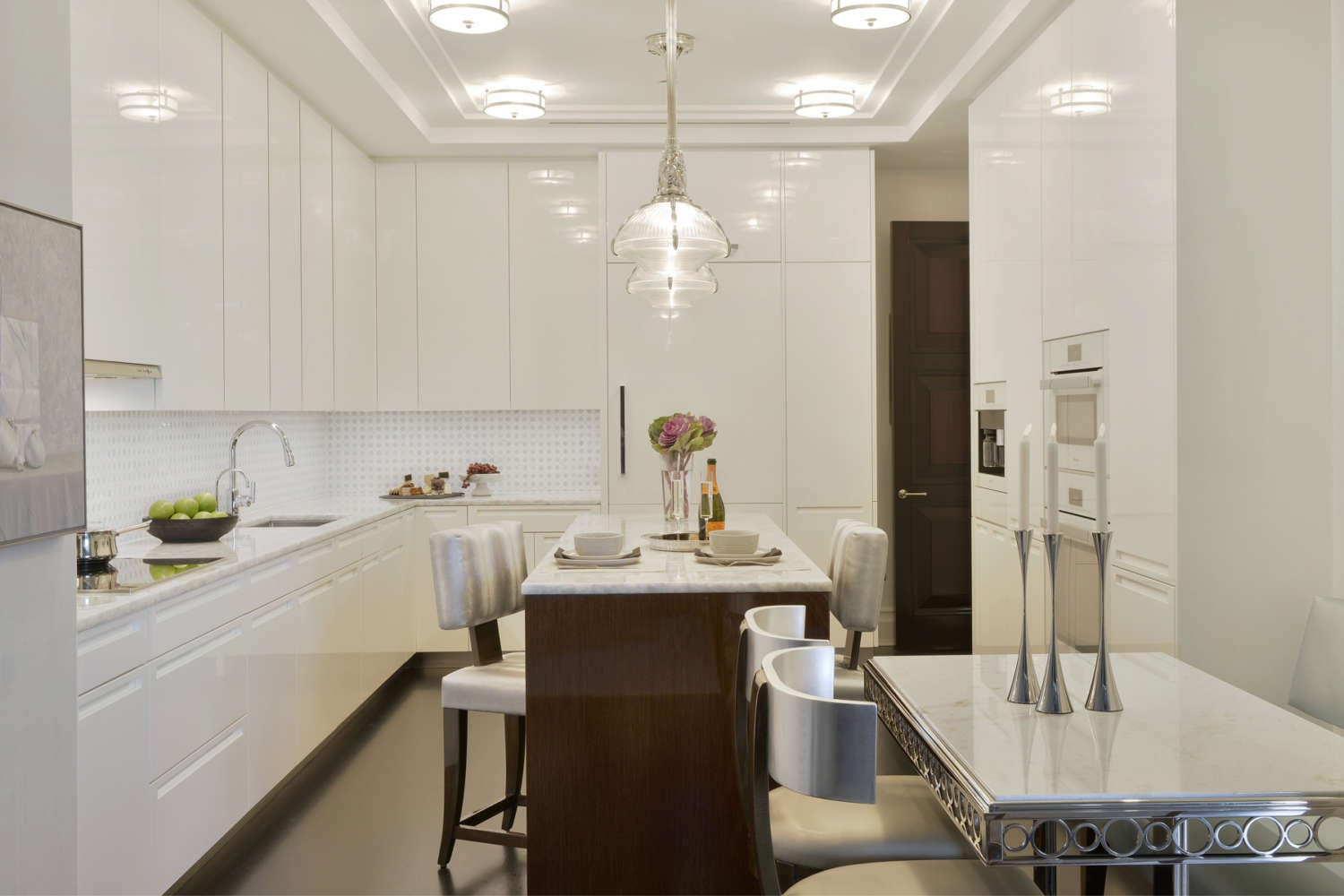 Contemporary kitchen features high gloss white, flat panel, frameless fully custom cabinets by Artcraft, built-in white appliances, integrated hardware and high gloss walnut island with seating. Design by Jeff Eakley of Bilotta Kitchens.
