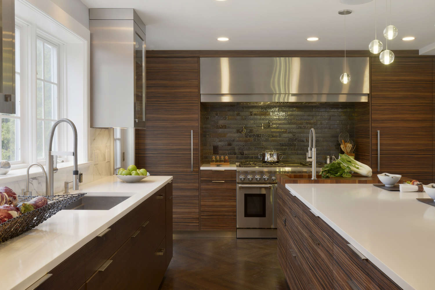 The large hearth with textural backsplash is a focal point of this contemporary kitchen. Fully custom cabinetry is flat panel, frameless Eva door style by Artcraft in a mix of Molveno Pine Laminate with horizontal grain and Cinque Terre laminate with horizontal grain. The kitchen also features alumasteel and glass accents. Design by Paula Greer, CKD, of Bilotta Kitchens.