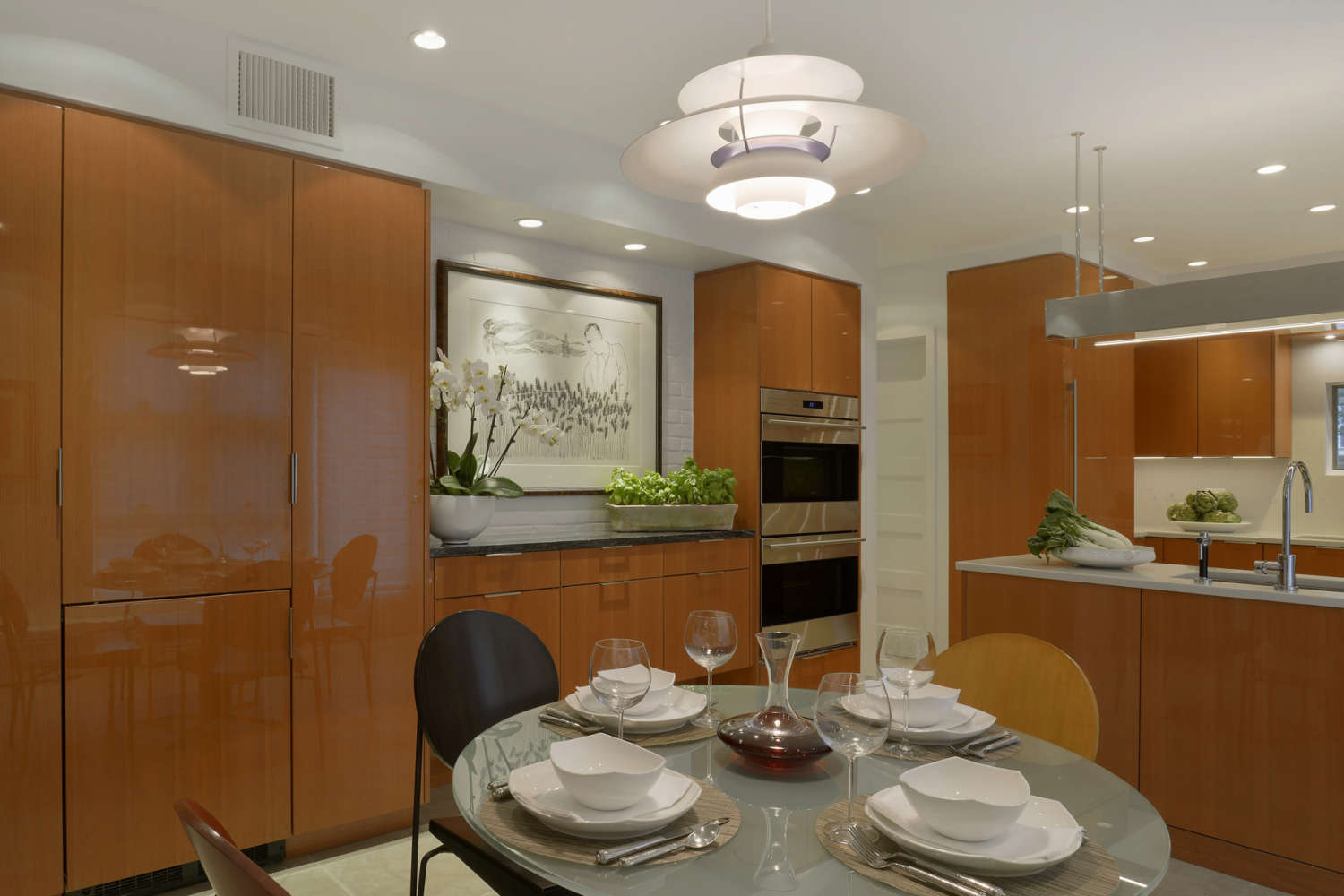 Contemporary kitchen features flat panel, frameless fully custom Artcraft cabinetry in high gloss rift cut cherry, brushed staineless hardware and a small eat-in area. Design by Goran Savic of Bilotta Kitchens.
