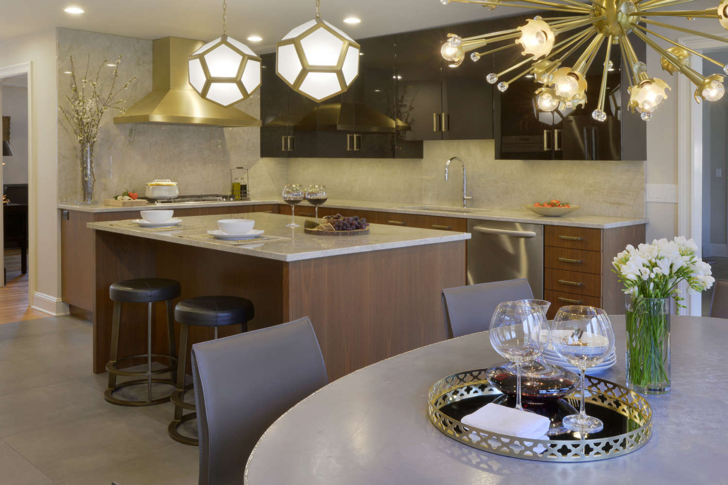 Contemporary kitchen features flat panel, frameless fully custom Artcraft cabinetry in a mix of walnut and high gloss black with gold accents, an island with seating and light quartz countertops. Design by Danielle Florie of Bilotta Kitchens.