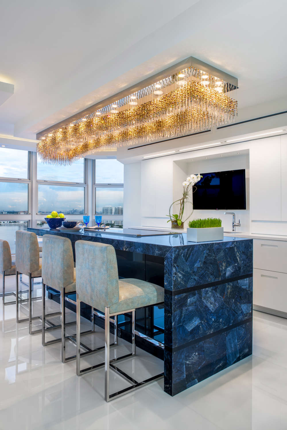 The island of this Florida penthouse kitchen features a Galaxy glass island with seating, a modern rectangular statement chandelier, and semi gloss white fully custom flat panel frameless cabinets by Artcraft. Design by Peter Bittner of Bilotta Kitchens.