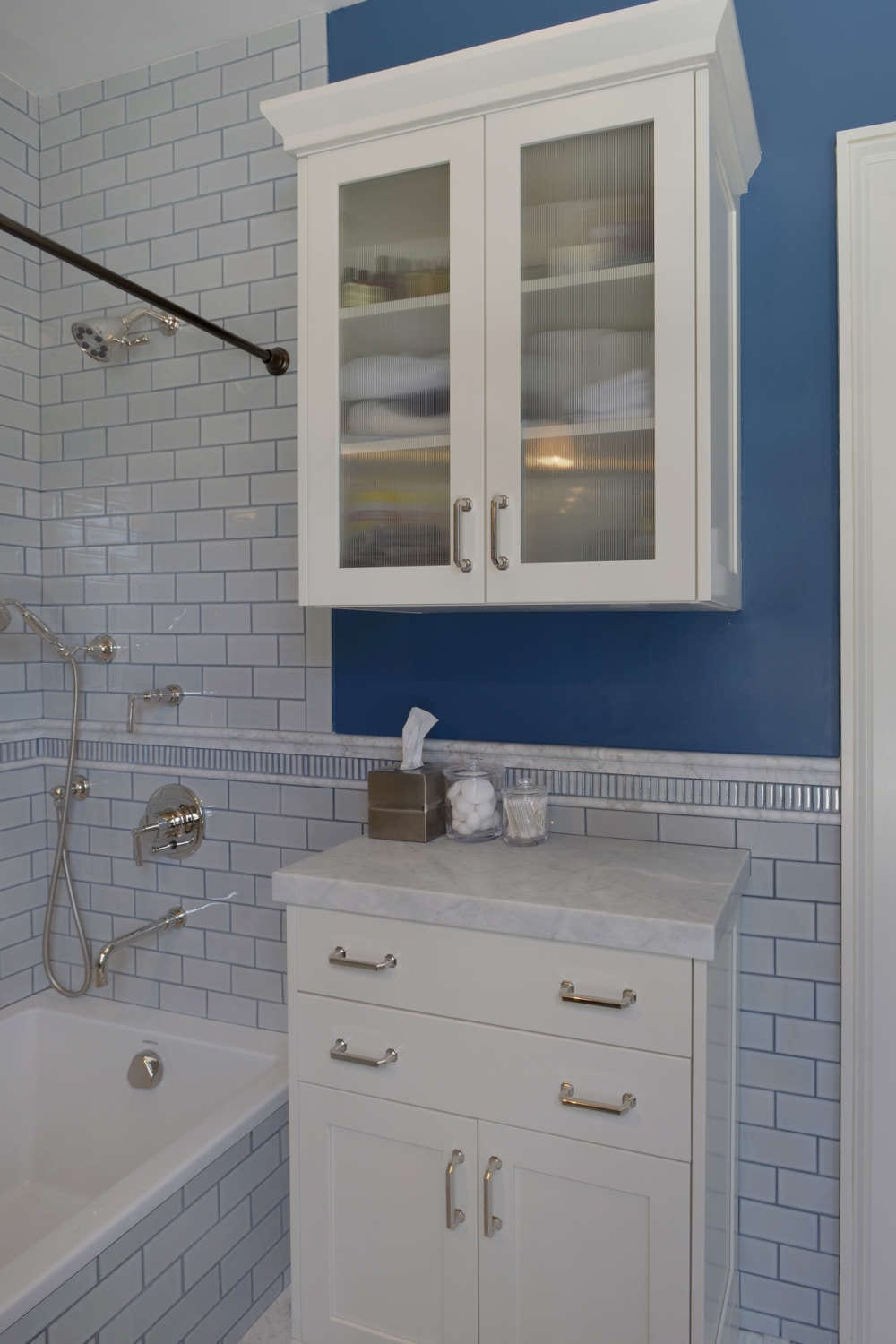 Transitional style secondary bath features white tile walls with grey grout, decorative chair rail tile and a bright blue painted accent wall. White painted, fully custom Bilotta Cabinetry vanity and storage cabinet with marble top and ribbed glass door fronts provide ample storage. Design by Paulette Gambacorta of Bilotta Kitchens.