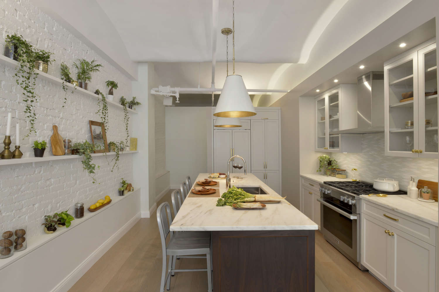 NYC loft kitchen features white painted brick walls with open shelving, oak flooring, high ceilings, gold accents and a mix of white painted and walnut shaker style frameless cabinets by Bilotta. Long center island has marble countertop and seating. Design by Tabitha Tepe of Bilotta Kitchens.