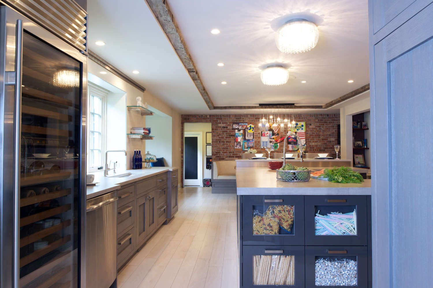 Expansive family-friendly kitchen features porcelain plank style tile flooring, exposed brick walls and a mix of shaker style Bilotta Cabinetry in rift white ash with a stain and flat panel, high-gloss blue-grey laquer finish cabinets by Artcraft. Island drawer feature glass fronts to easily iedntify the contents. Design by Jeff Eakley of Bilotta Kitchens.