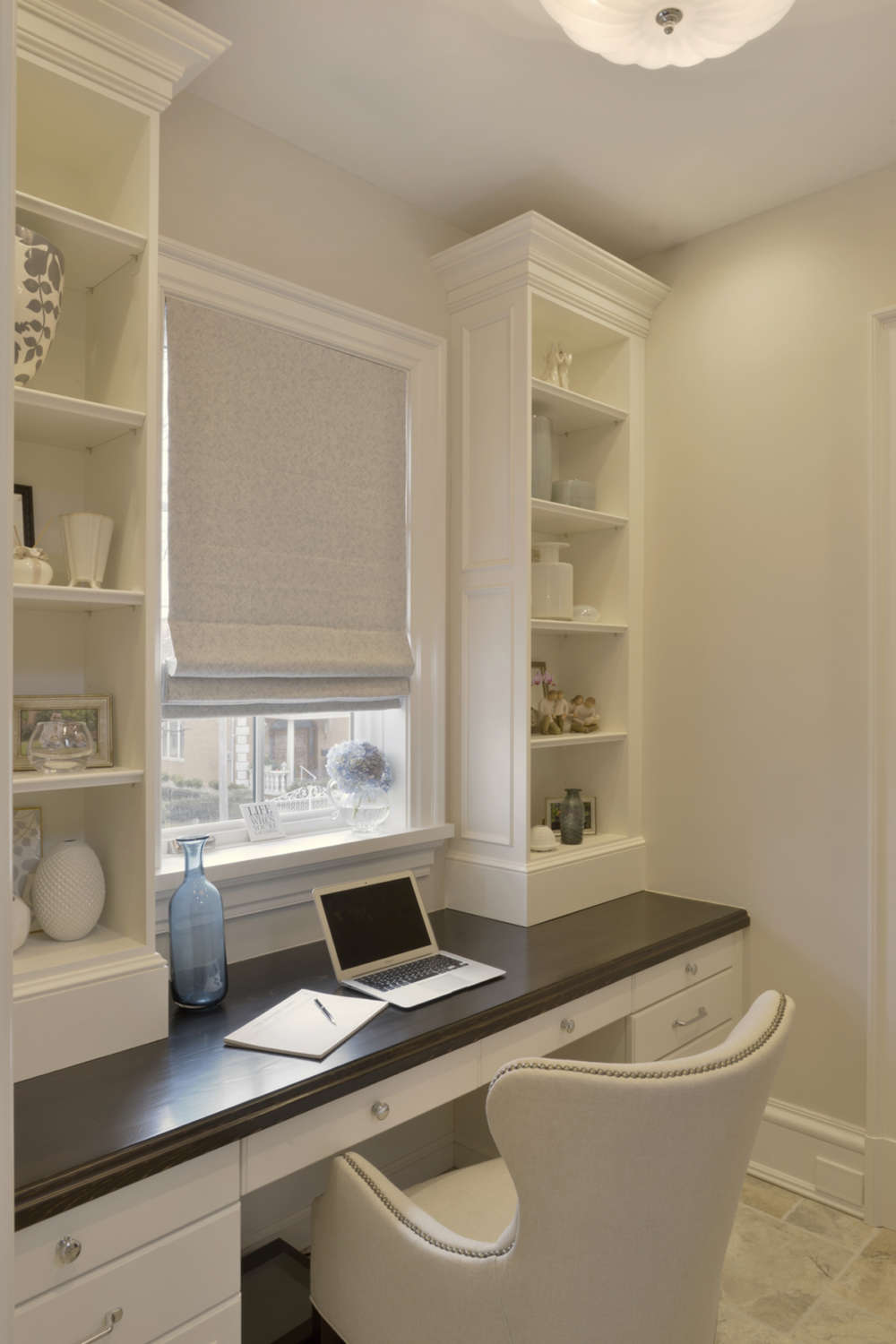 Home office features a classic white painted, custom desk with round polished stainless hardware and espresso brown top. The desk is positioned under a window with flax colored roman fabric shade flanked by custom white painted built-in open shelving. Design by Tom Vecchio of Bilotta Kitchens.