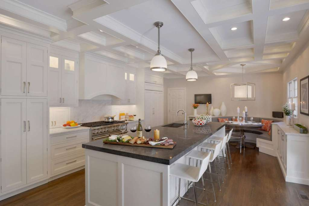 Traditional kitchen with white painted Bilotta cabinets, coffered ceiling, large island with seating and circular banquette area. Silver accents on pendant lights complement the silver cabinet hardware. Designed by Fabrice Garson of Bilotta Kitchens.
