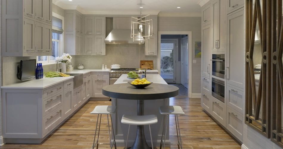 U-shaped kitchen with breakfast nook features coffered ceiling with silver-accented pendant lighting, Gray granite countertop, and white painted fully custom Bilotta cabinetry with silver hardware. Upper cabinets are lit, reflecting light to the white marble backsplash.