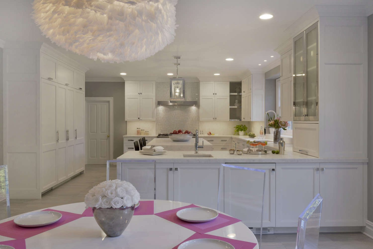 All white kitchen features fully custom frameless shaker style double tiered white painted Bilotta Cabinetry with open corner shelves and some frosted glass fronts, an island and penninsula with white marble waterwall countertop and polished stainless accents. The eat-in dinning area features a large white feathered pendant light. Design by Danielle Florie of Bilotta Kitchens.