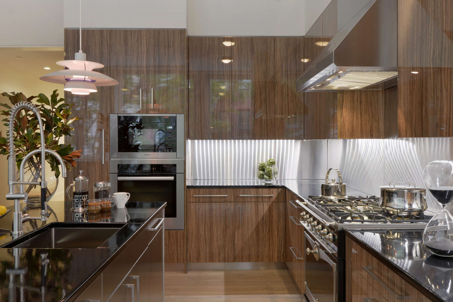 NYC L-shaped loft kitchen features a mix of high gloss olive wood and brushed alumasteel custom cabinetry by Artcraft in flat panel, frameless style. The design incorporates dramatic lighting, black granite countertops and light oak flooring. Design by Randy O'Kane, CKD, of Bilotta Kitchens.