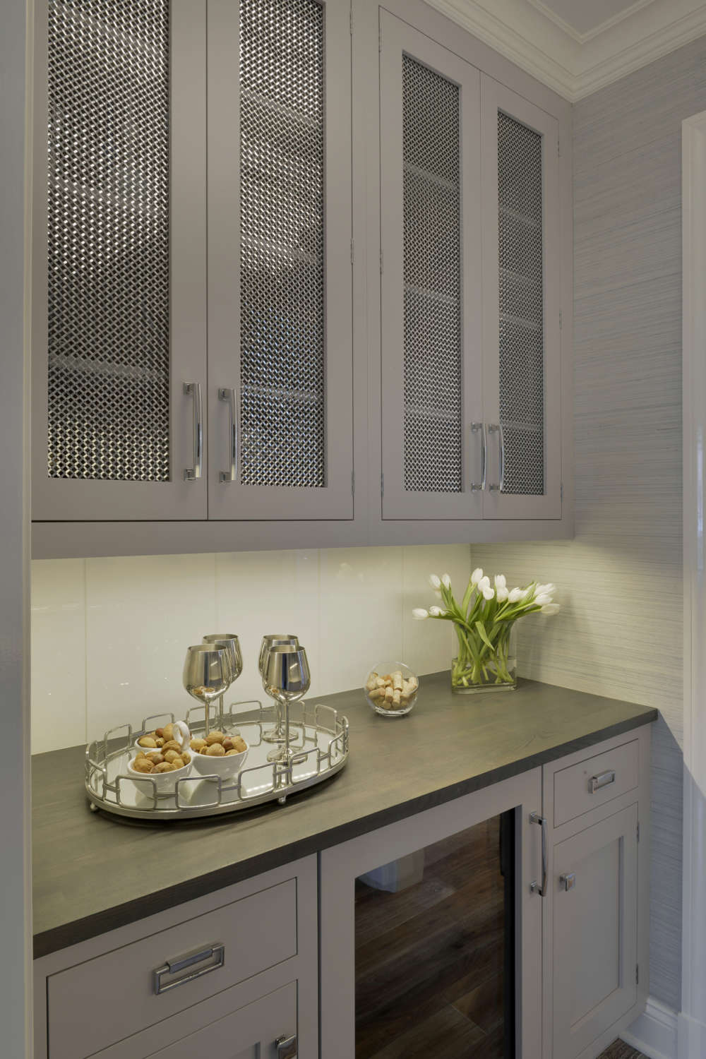 Butler's pantry features shaker style, light grey painted Biotta cabinetry with metal door inserts and brushed stainless hardware, grey walls, espresso countertops and a beverage refrigerator. Design by Randy O'Kane, CKD, of Bilotta kitchens.