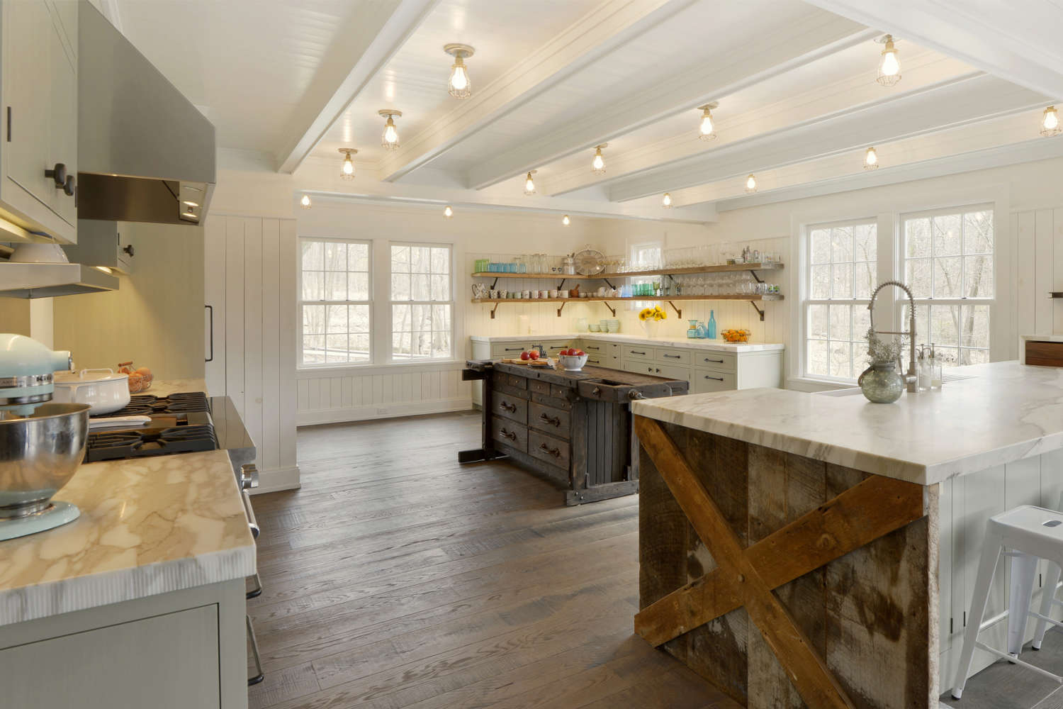 Expansive country kitchen features white beadboard ceiling and walls, exposed lighting, oversized windows, wood plank flooring, fully custom flat panel inset pale green painted Bilotta Cabinetry with oil rubbed bronze hardware, open shelving, white marble countertops and a rustic custom wood island. Design by Paulette Gambacorta of Bilotta Kitchens.