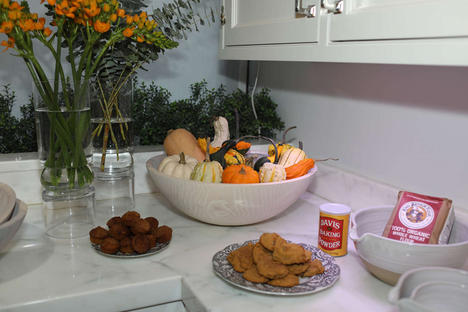Plates of cookies and white bowls filled with mini pumpkins and gourds.