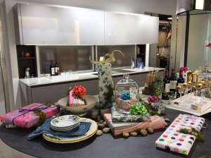 Wrapped holiday gifts, wine bottles and plates are arranged on a black quartz topped kitchen island.