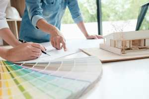 Architect and designer review kitchen plans and color chips.