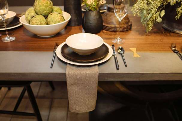 place setting of Calvin Klein's Cargo collection in beige and brown on a wood and concrete table