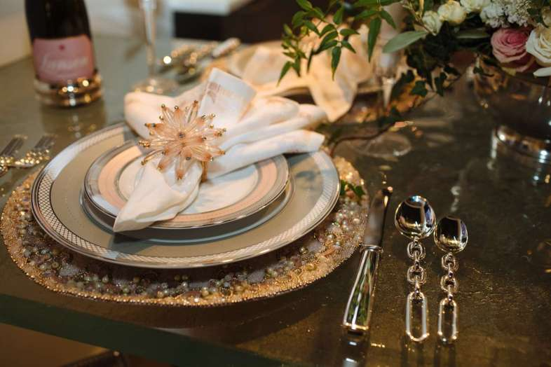 place setting of Ralph Lauren's Silk Ribbon china in both slate and pink coupled with chunky chain-link flatware in chrome all accented by a beaded place mat and 3-dimensional beaded pink star-like napkins holder