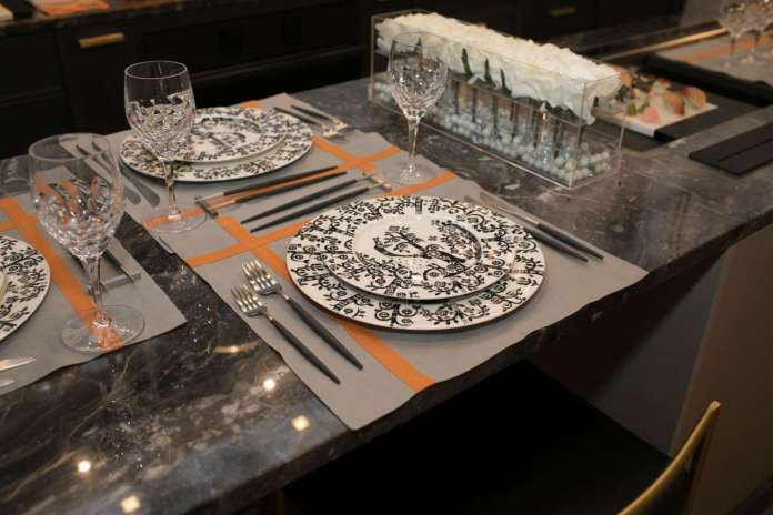 China featuring a stylized motif of birds and trees called Taika Black by Iittala coupled with grey and orange place mats and stainless steel and resin flatware