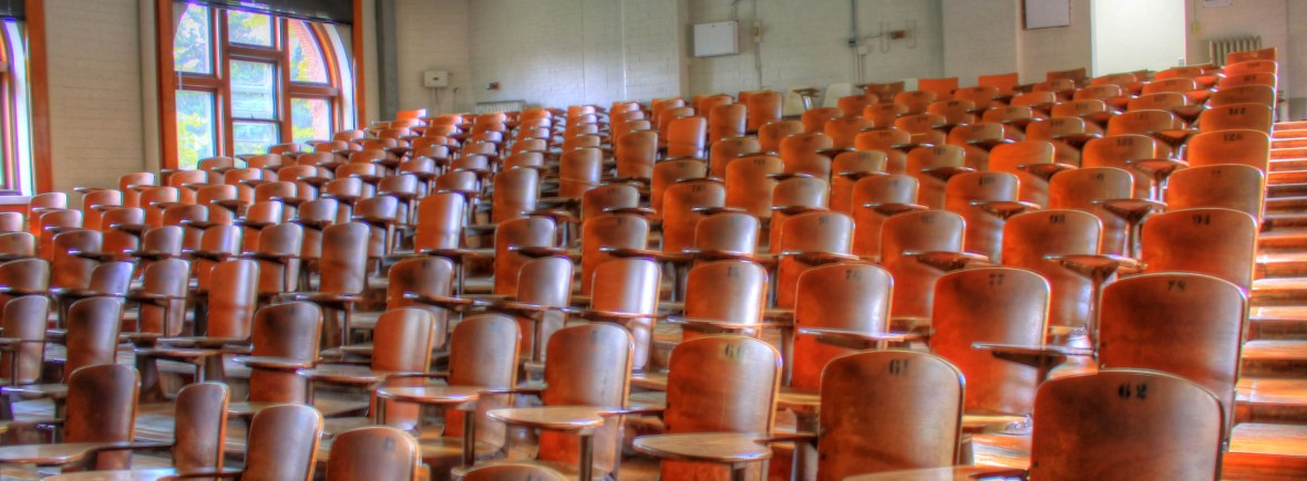 empty wooden seats in a large lecture theatre