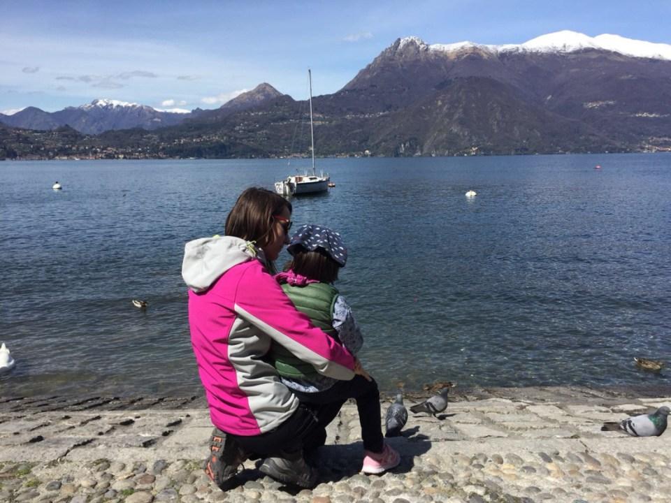 mamma abbraccia la figlia durante una gita sul lungolago di Lecco in Lombardia
