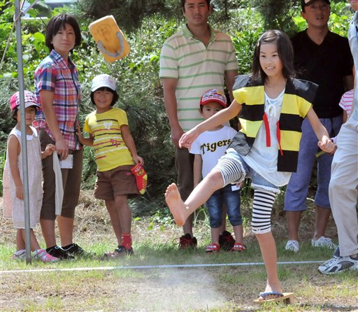 "Girl competes in ""geta"" sandal toss competition"