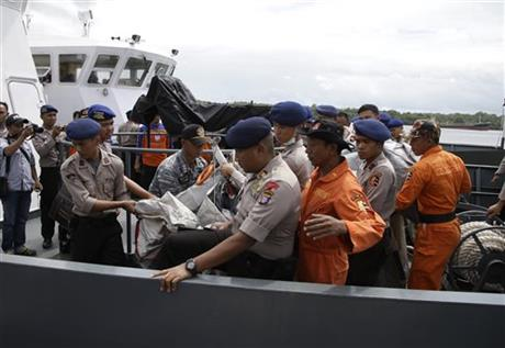 Indonesian police carry parts of an airplane found floating on the water near the site where AirAsia Flight 8501 disappeared, at Kumai port in Pangkalan Bun, Thursday, Jan. 1, 2015. The weather improved as the search resumed Thursday for the victims with officials trying to locate the fuselage of the plane that crashed in the sea four days ago. (AP Photo/Achmad Ibrahim)