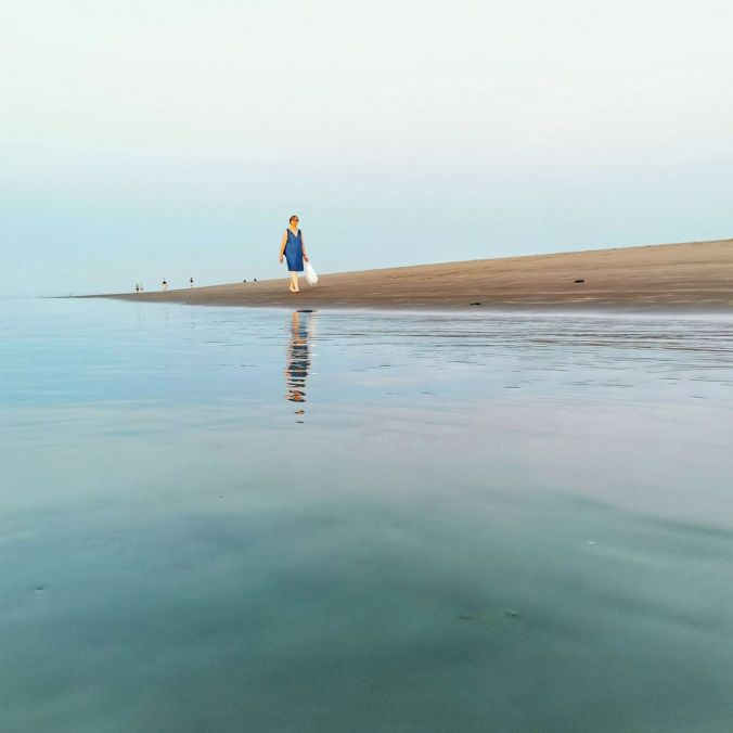 Bea walking along the beach at dusk, her reflection showing in the water