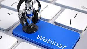 A pair of headphones resting on a podcast mic placed on a webinar button