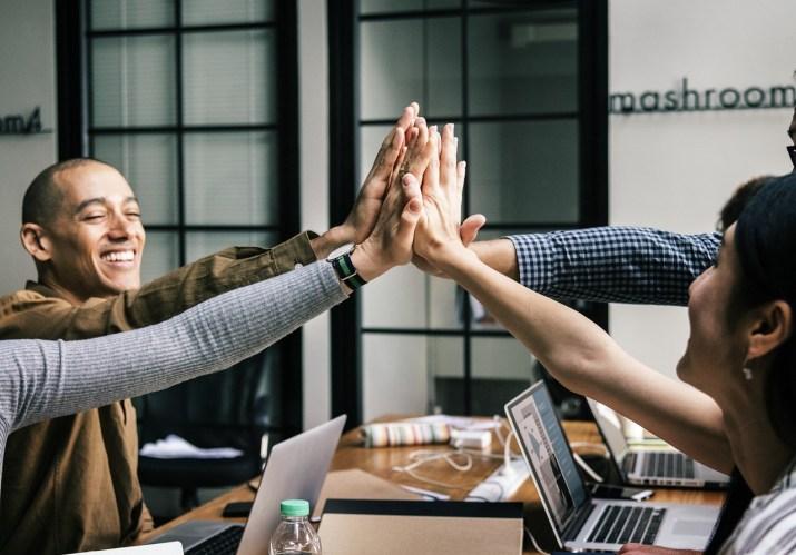 Sonriendo colaboradores de cinco en alto durante este tutorial de WordPress.