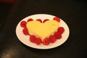 Heart shaped cheesecake with raspberries