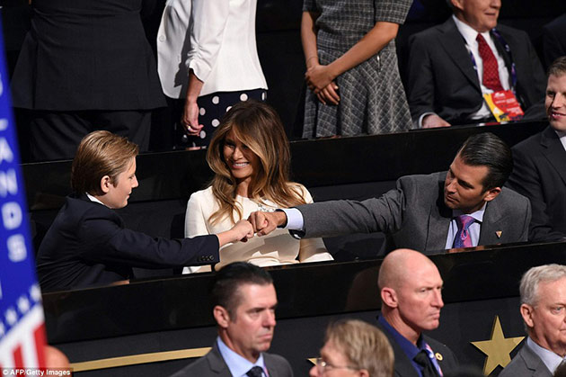 Barron Trump and Donald Trump Jr. sharing a fist punch while meeting each other.
