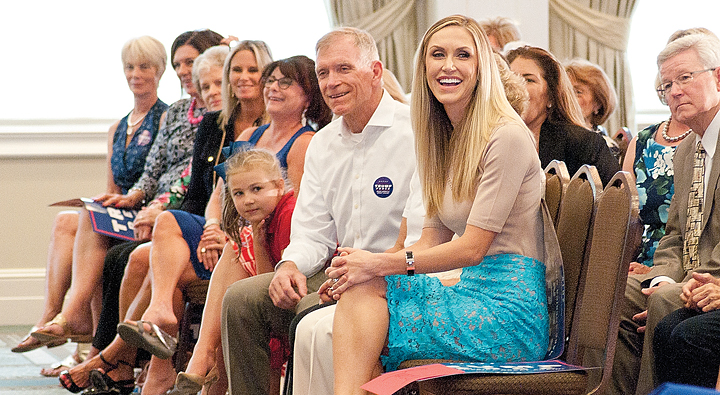 Lara Trump sits in the audience with her father and other family.