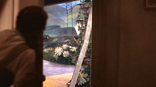 Picture of Dorothy from Wizard of Oz peeking out from house and seeing color, just after landing in Munchkinland