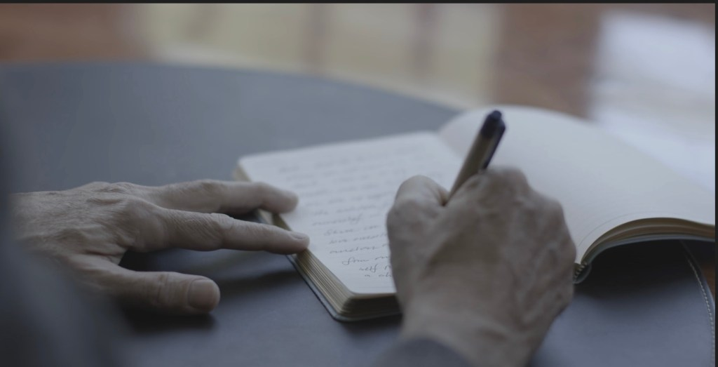 A picture of Dr. John Budin Writing at his desk