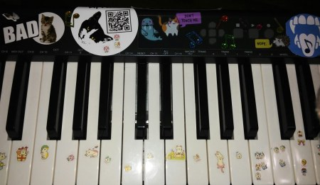 close up of festive synthisizer keyboard covered with kitty stickers, used by BipTunia to make the first 4 BipTunia albums.