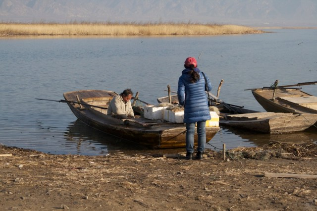 Yuxia speaks to the local fishermen about life at Ma Chang...