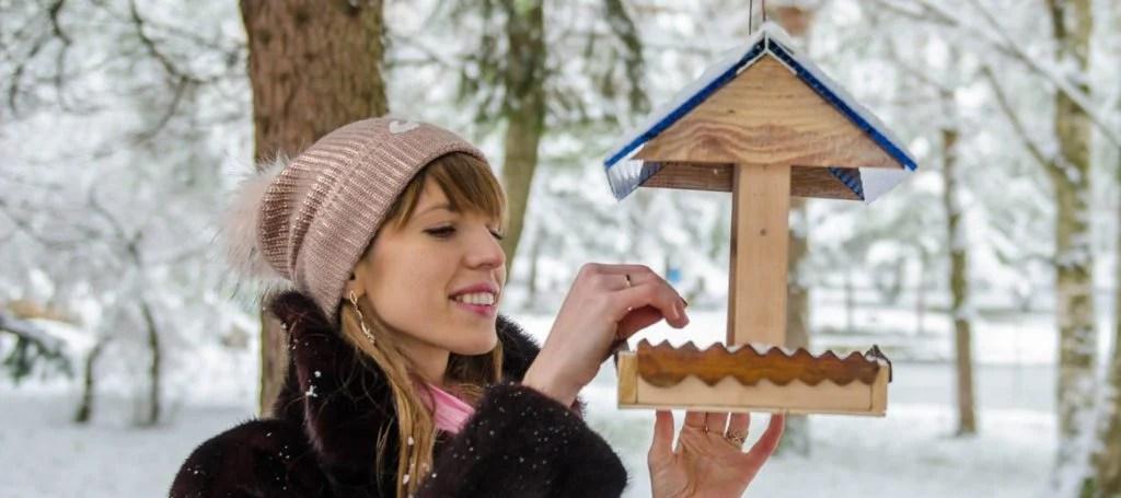 girl feeding birds in her yard