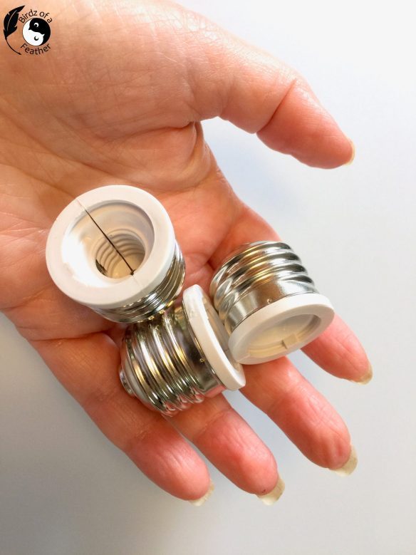 Hand holding standard base adapters used in plastic packaging for cement planter molds