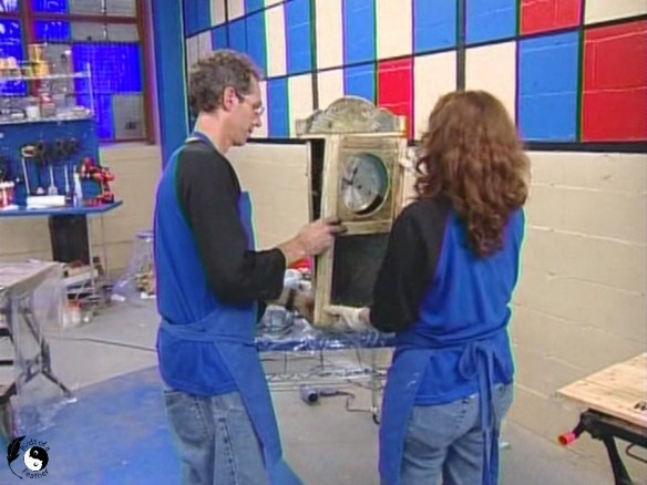 Shows two people reattaching the door of a wall clock for decoupage on wood project