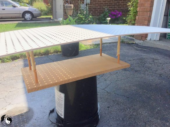 Large pegboard sitting on top of a paint jig made with wood and dowels