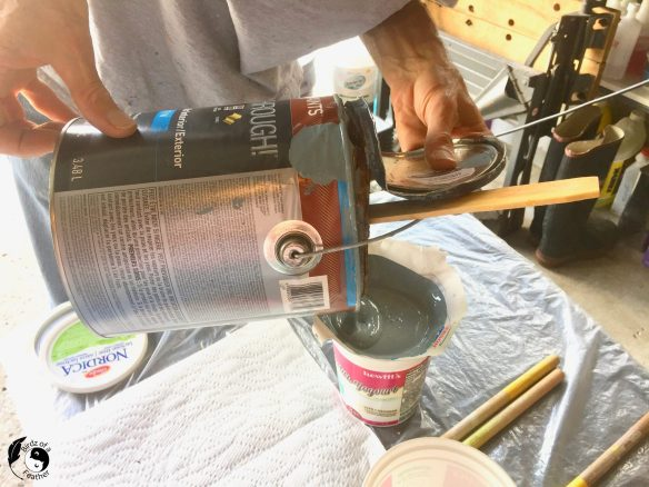 Pouring paint through a filter to prepare for Paint Using a Spray Gun